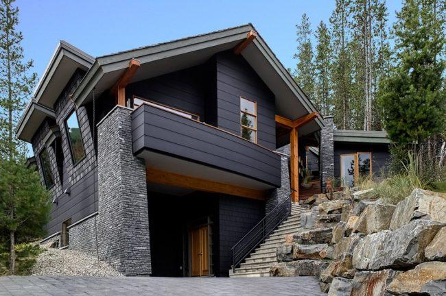 Extérieur de la maison avec murs en pierre grise, détails peints en gris foncé et bois naturel