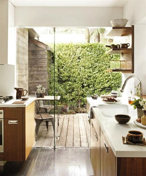 Cuisine avec armoires en bois et grande fenêtre sur le jardin vert