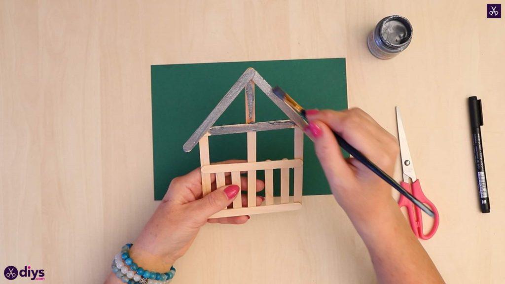 Le bâton de Popsicle ornement de maison commence le processus de peinture