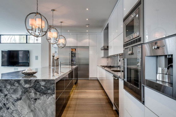 Décor d'îlot de cuisine en marbre et armoires hautes et basses en blanc brillant